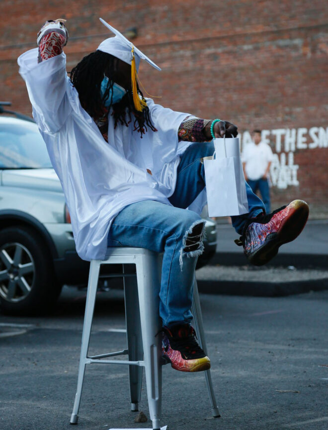 A Lighthouse students pumps his fist in the air, dressed in a white graduation gown and cap with his dreds done just right.